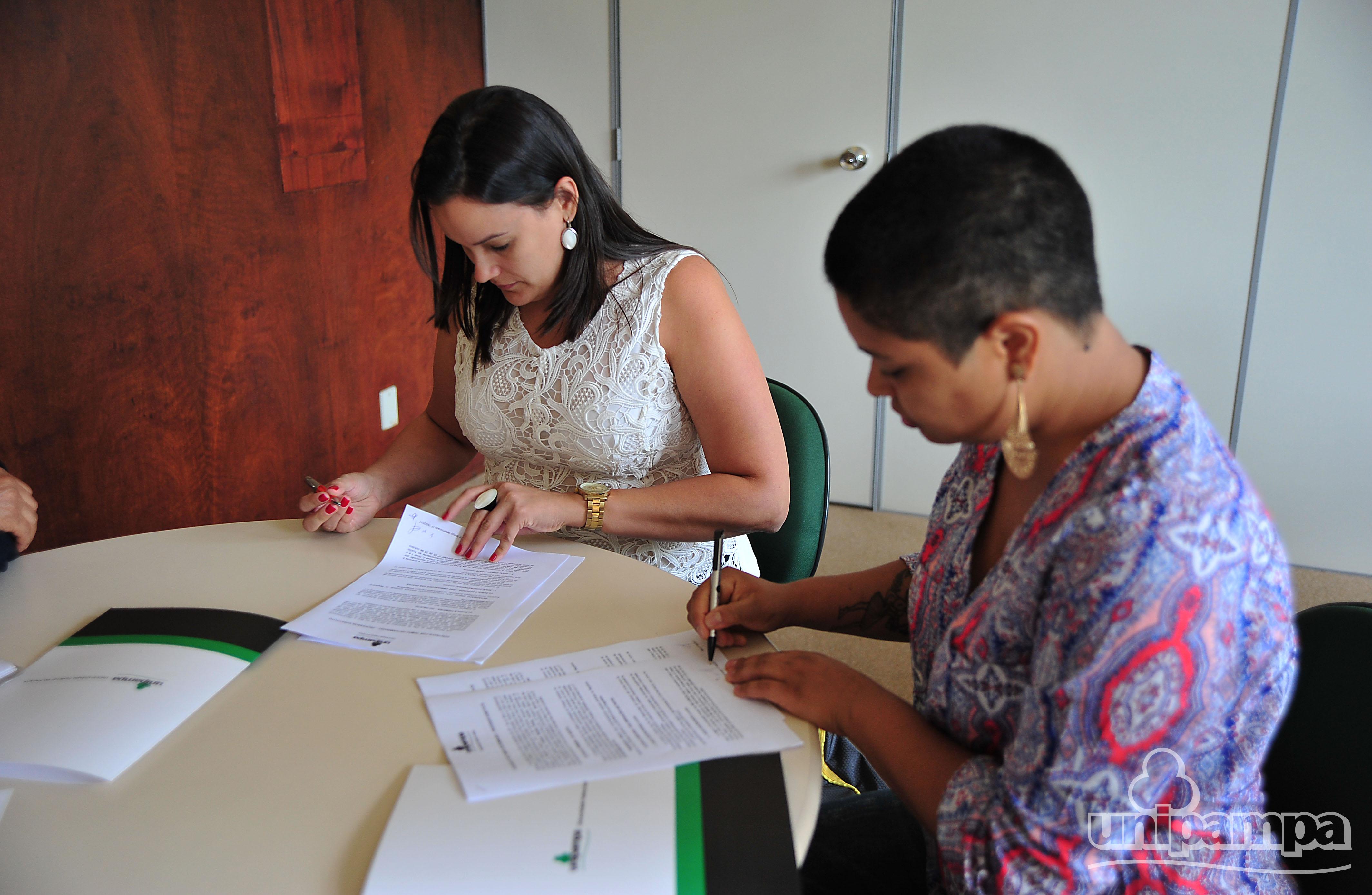 Duas mulheres sentadas em uma mesa branca, de cabeça baixa, com a caneta na mão e segurando um papel.