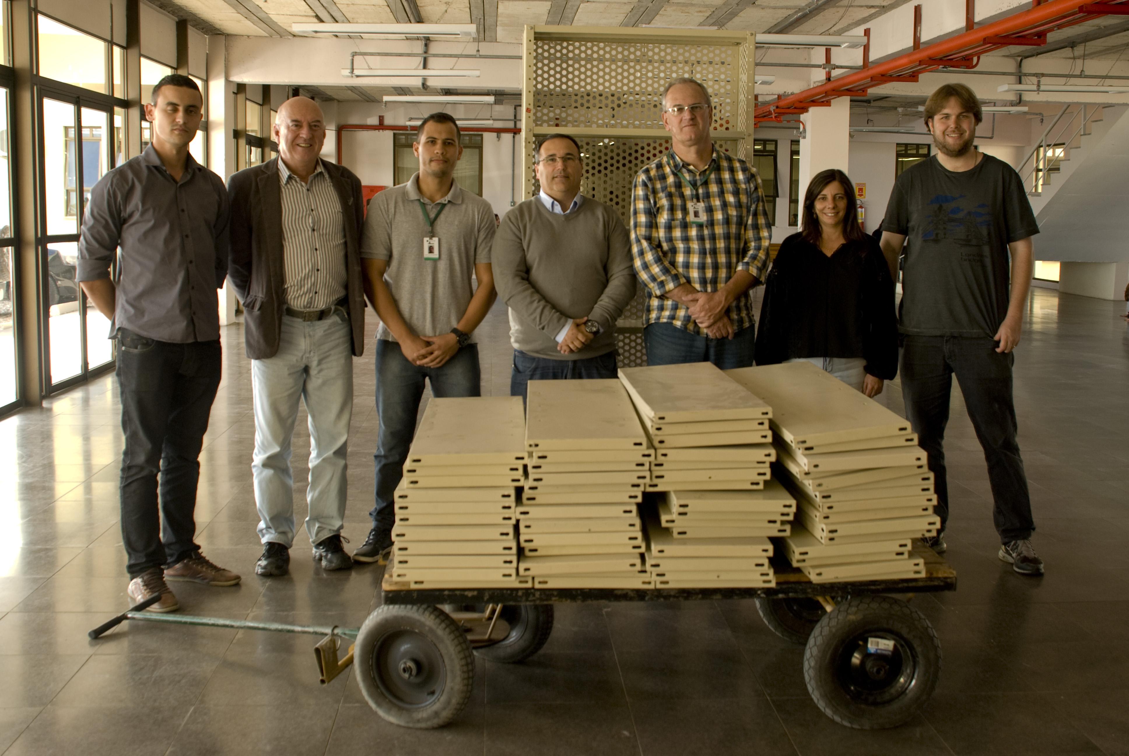 Seis pessoas se encontram atrás de um carrinho com prateleiras em madeira na cor bege.