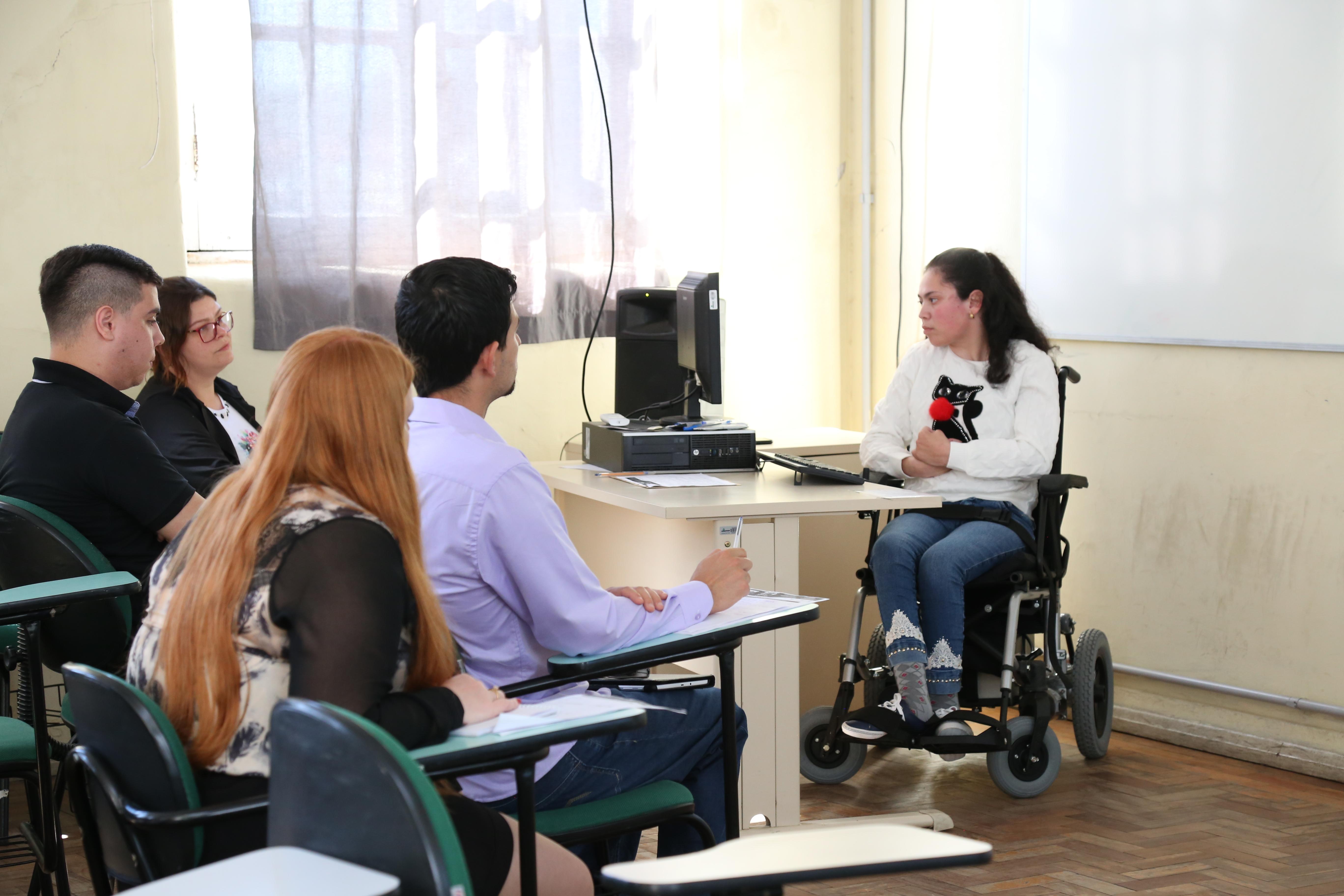 Ao fundo, aluna usuária de cadeira de rodas em frente ao computador. À frente, parcela do público acompanhando a apresentação.