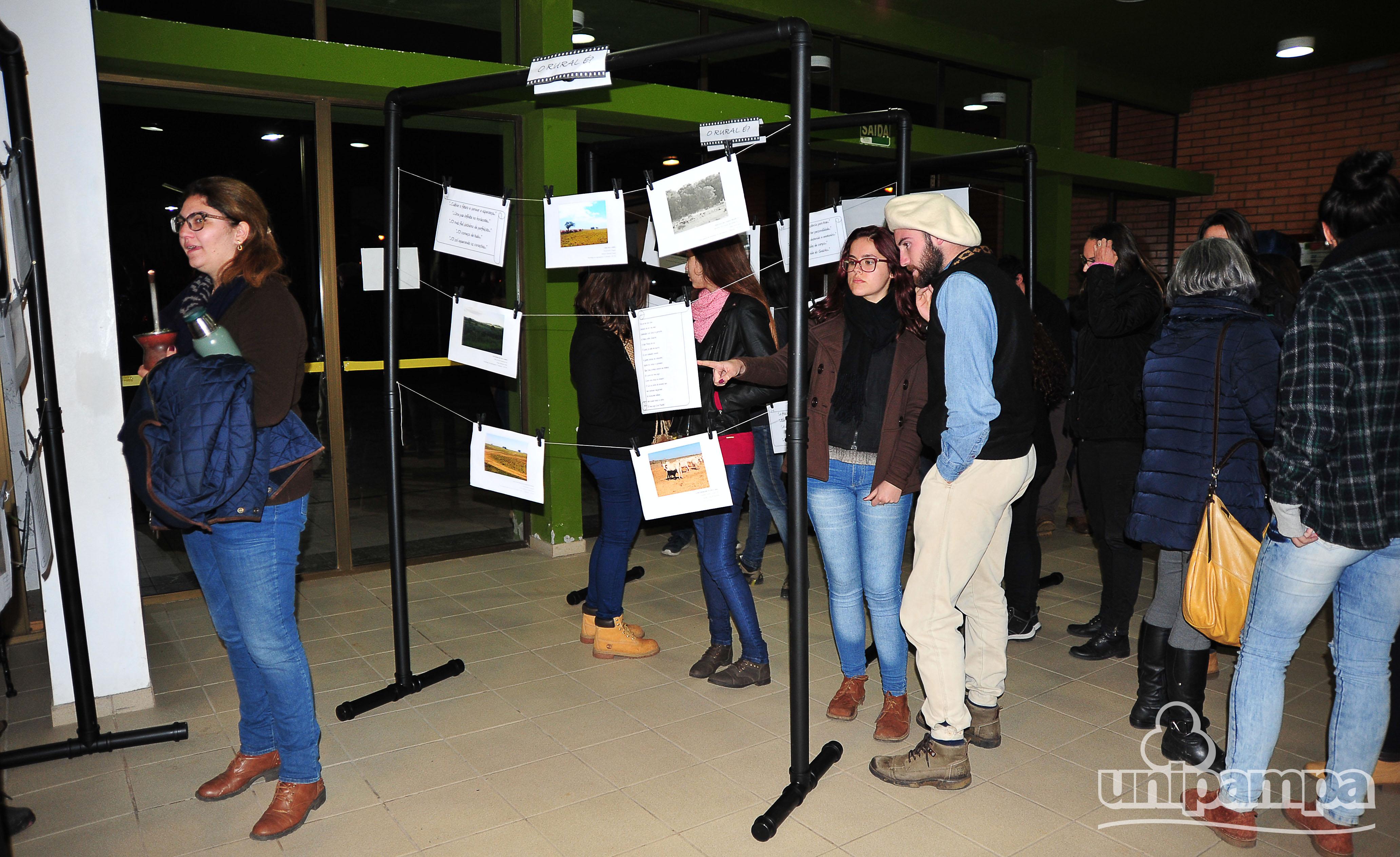 Pessoas em frente aos expositores, olhando as fotos