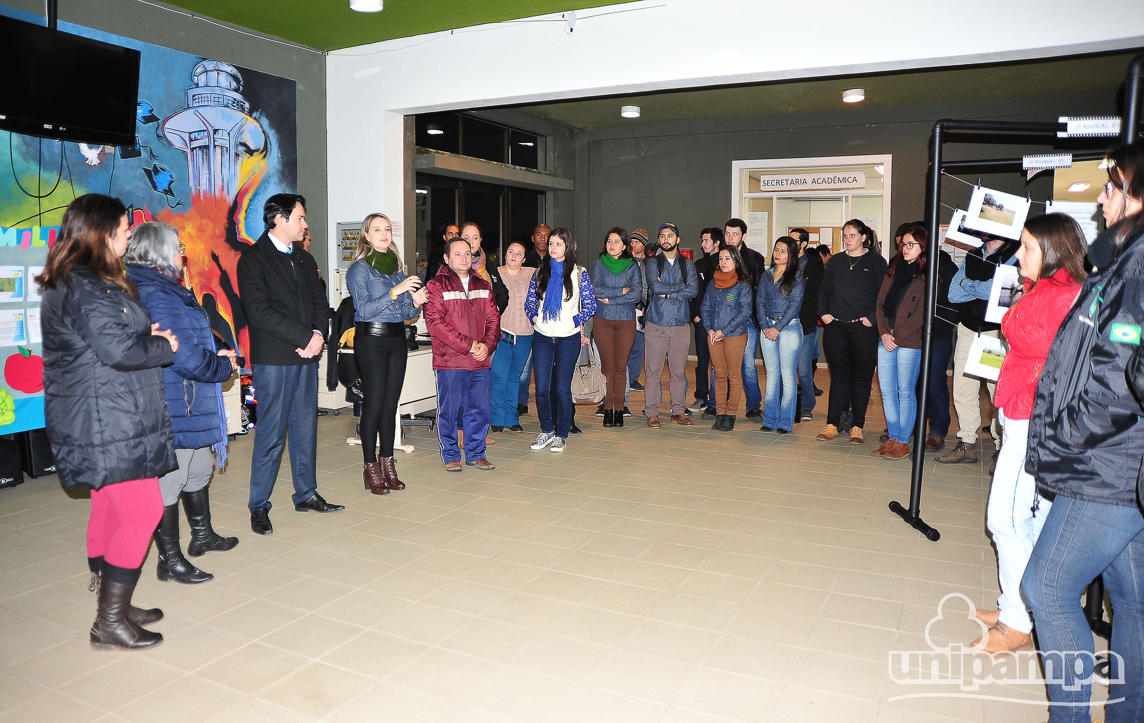 Pessoas em pé, formando um semicírculo durante cerimônia de abertura do evento