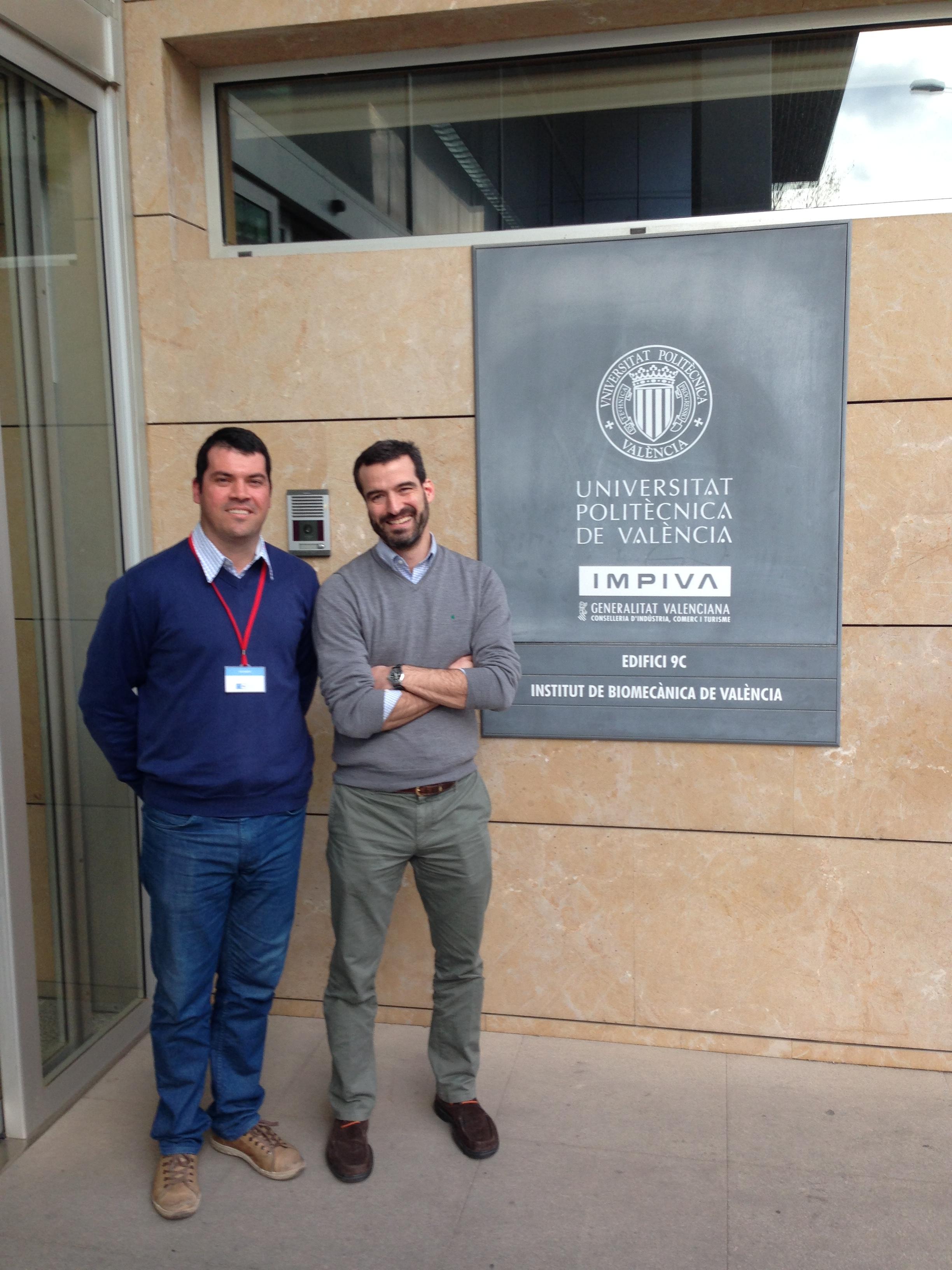 dois homens, o da esquerda sendo o professor Felipe carpes, posam para a foto ao lado de placa do Instituto de biomecânica de Valência