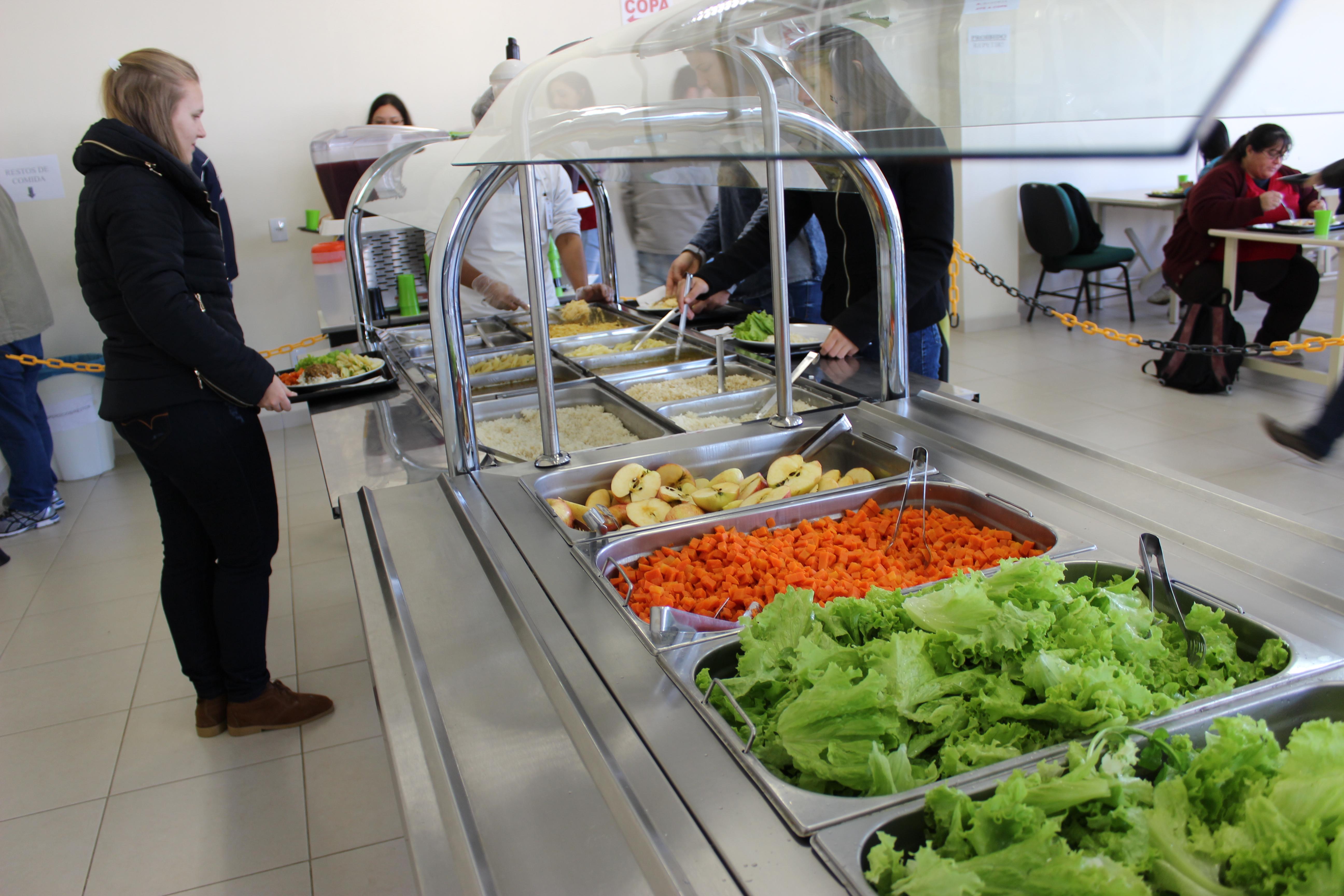 Balcão com bufê de alimentos dispostos para serem servidos.