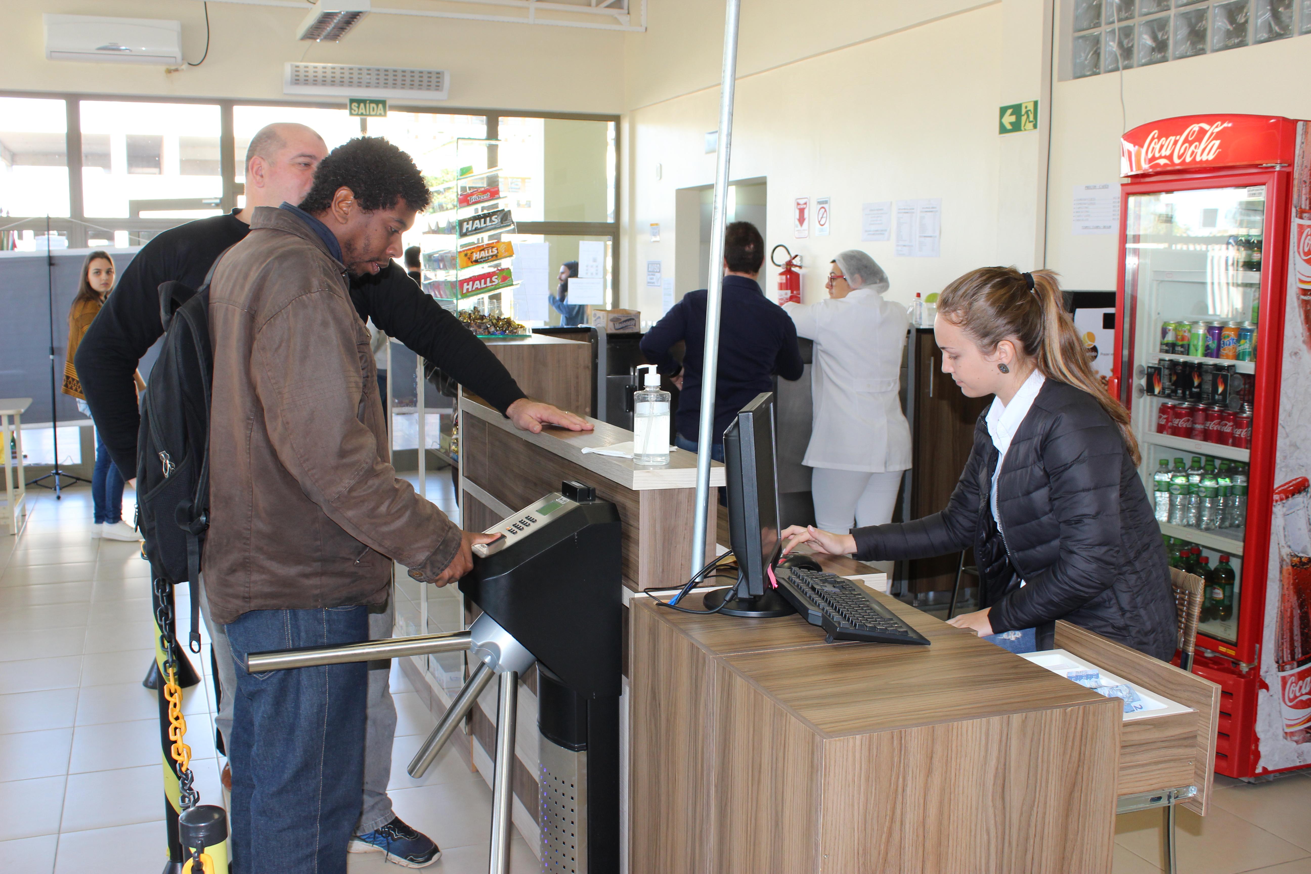 Pessoas fazendo pagamento no caixa do RU e passando pela catraca de identificação biométrica.