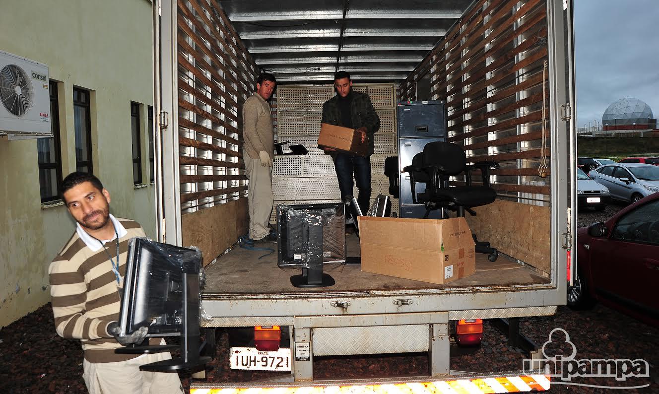 Caminhão com baú aberto e equipamentos sendo descarregados