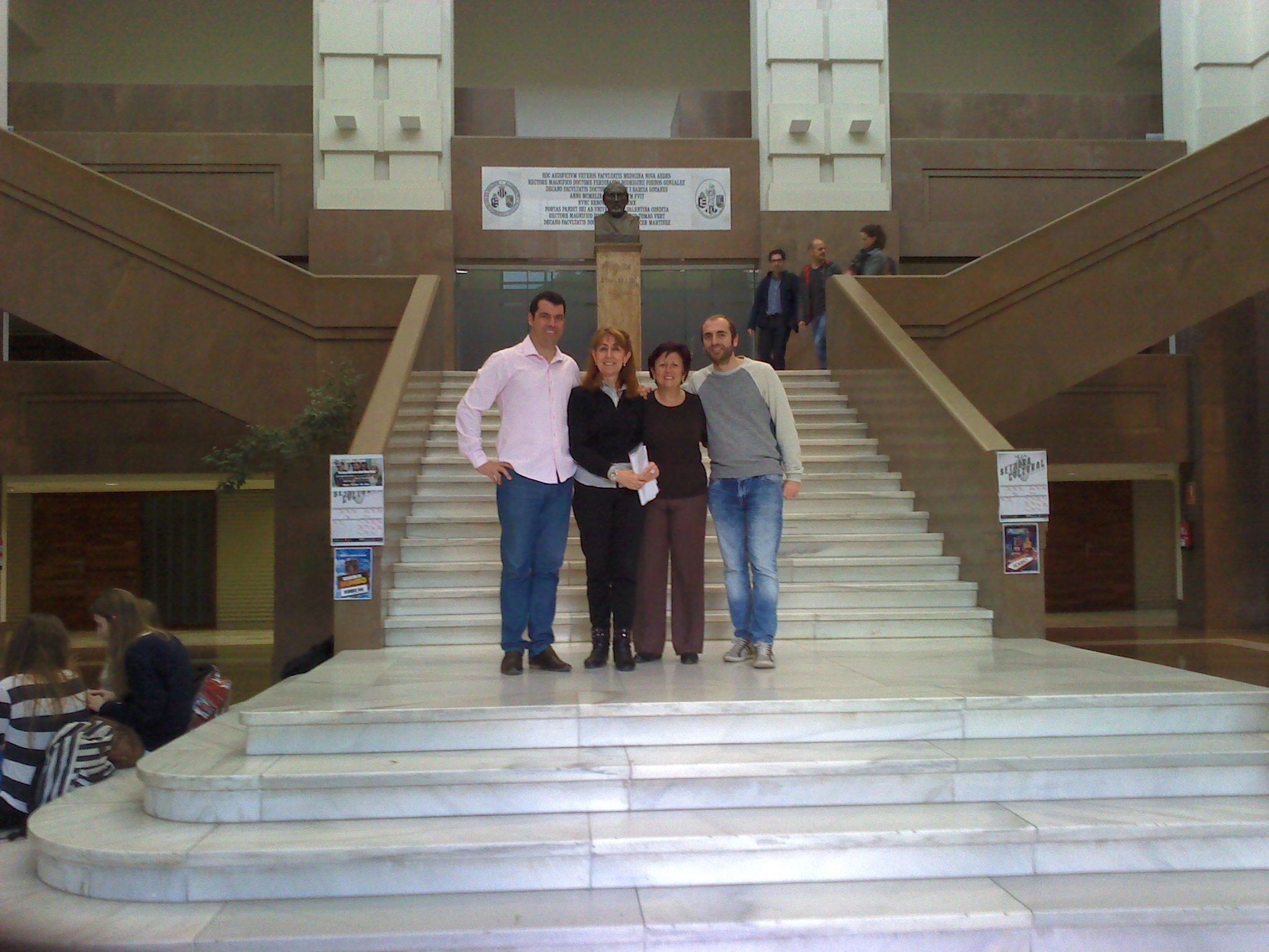 quatro pessoas posam para foto em frente a escadaria.