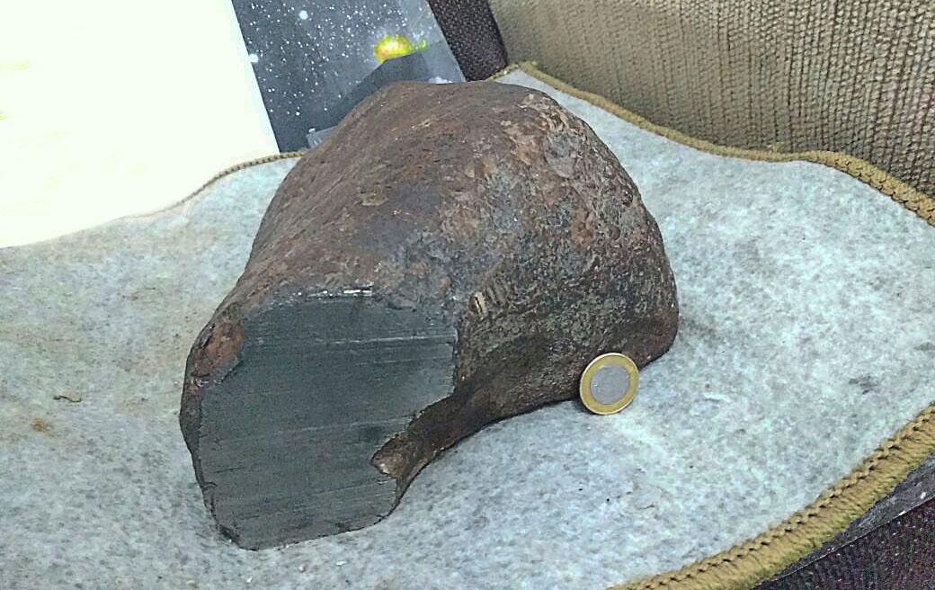 Meteorito de cor escura sobre um tapete cinza e comparado à uma moeda de um real. O meteorito possui 27 quilos.