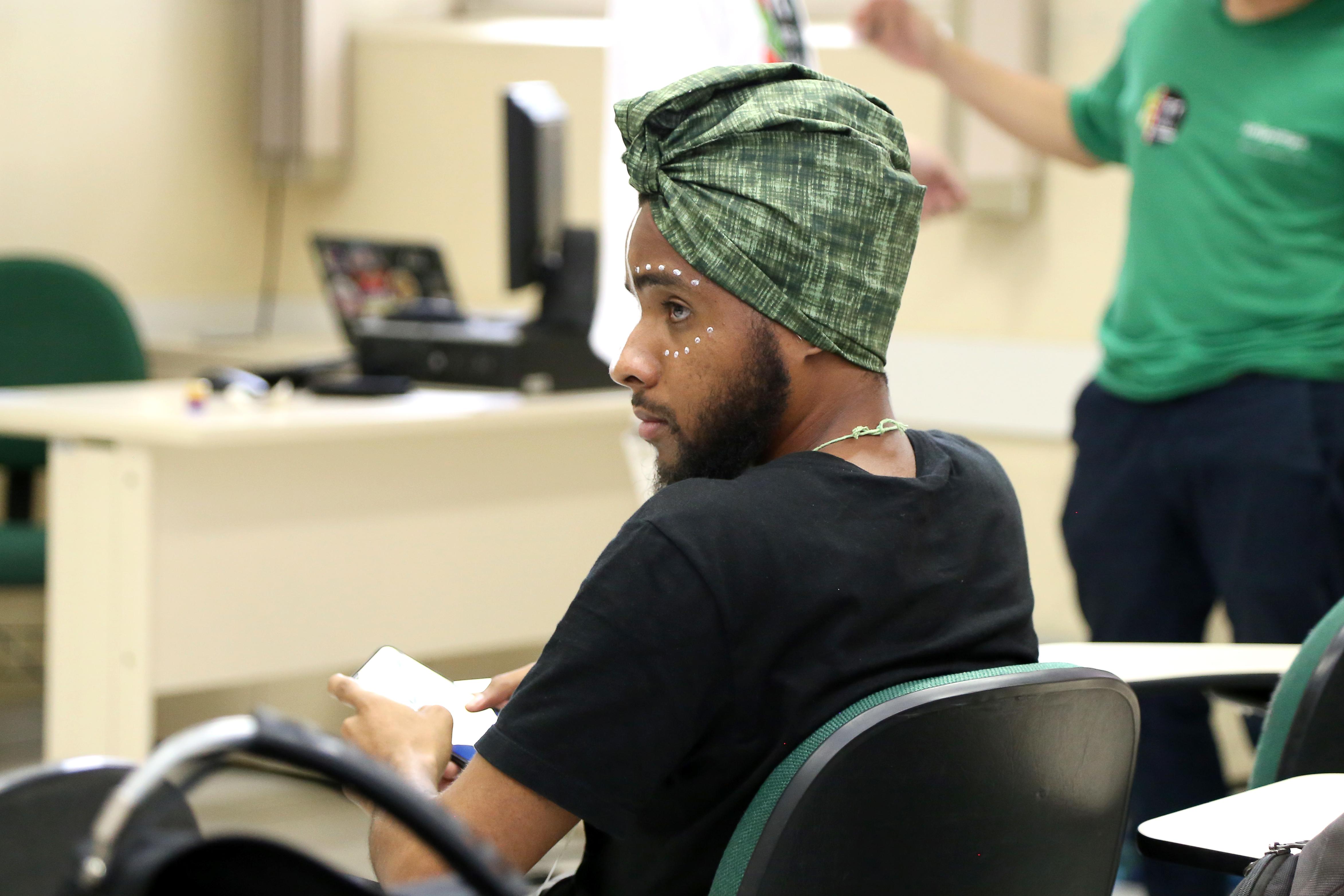 Um homem negro, jovem, sentado de costas, usando turbante e com pintura nos olhos.