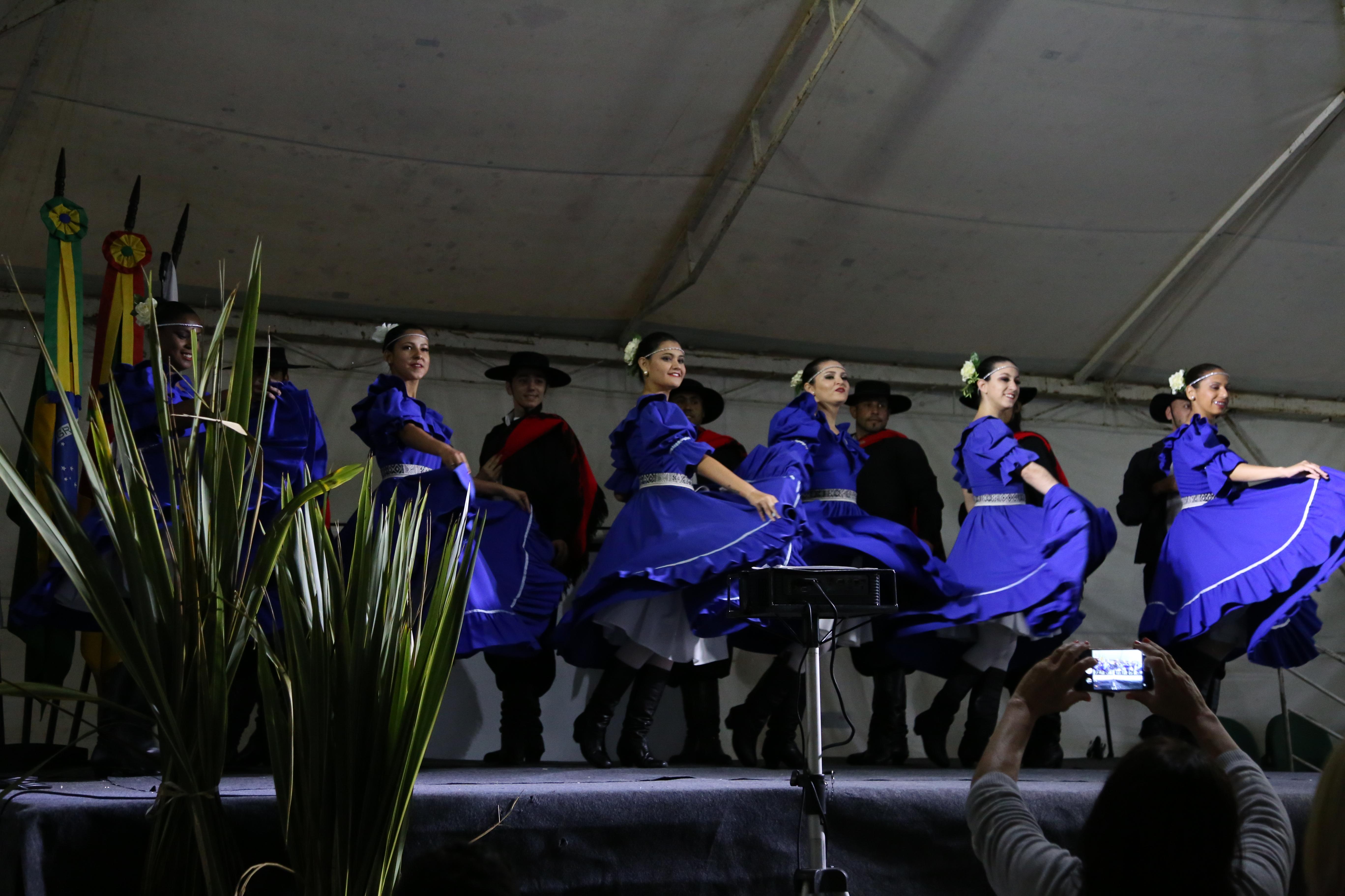 Doze pessoas dançando com trajes gaúchos. Mulheres a frente e homens ao fundo.