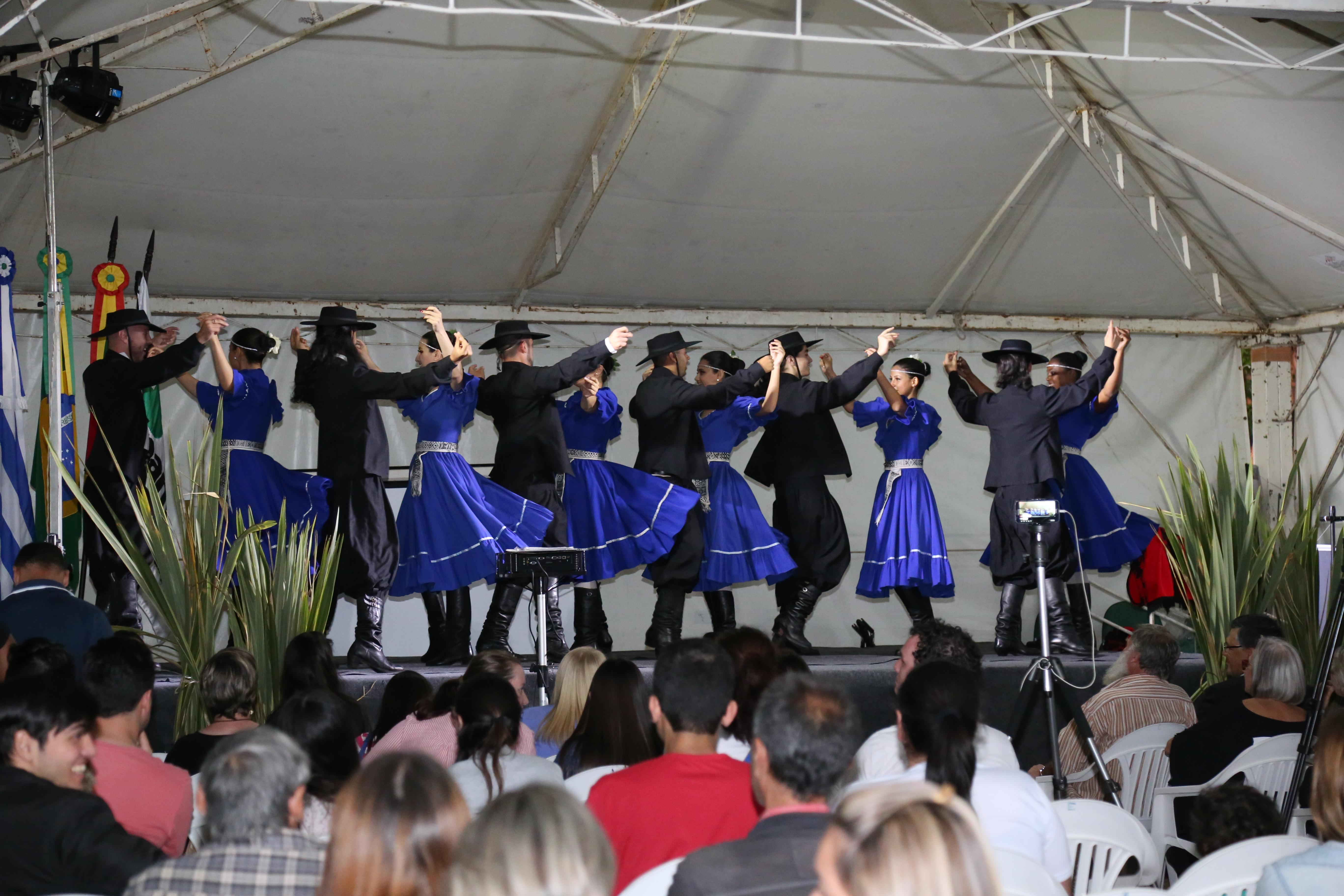 Seis casais dançando no palco usando trajes gaúchos, com cores azul e preto. Público a frente assistindo.