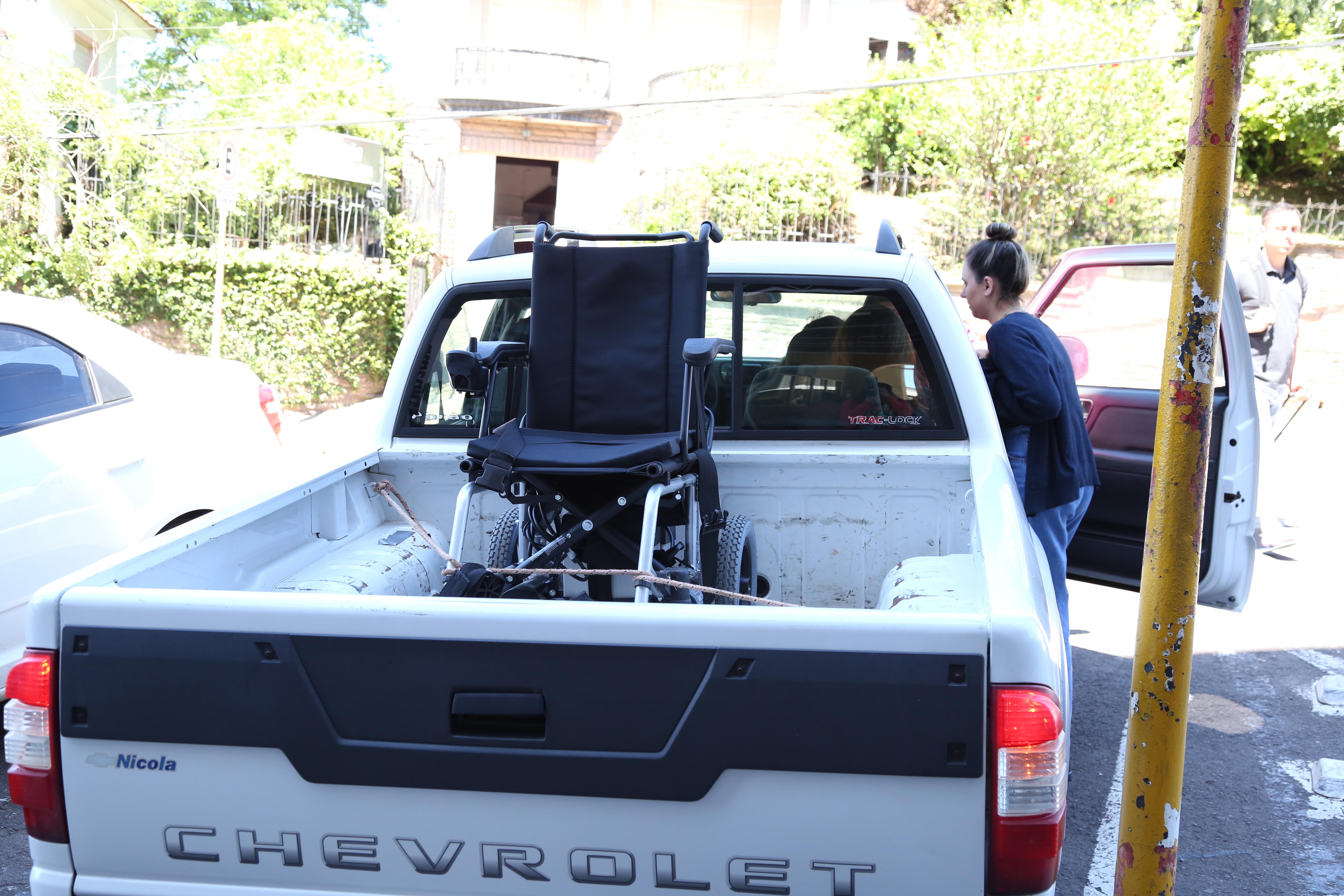 Camionete branca. Cadeira de rodas sob a caçamba.
