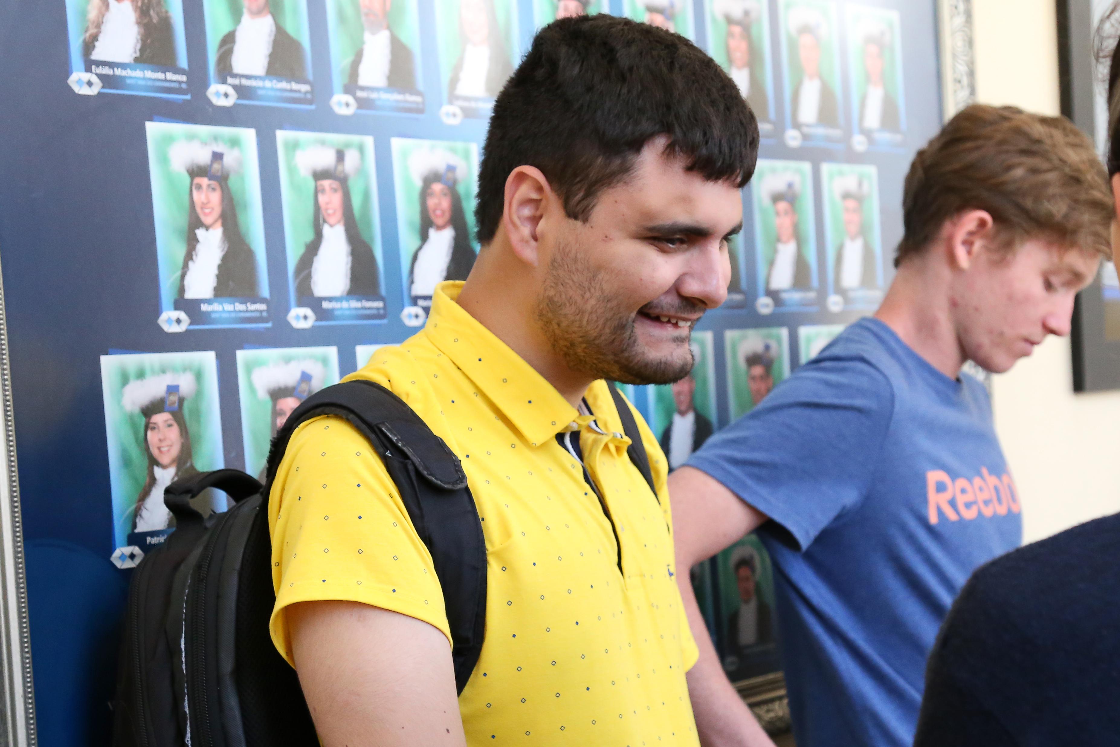 Jovem homem sentado, braços cruzados no colo, cabelo castanho, curto, olhos fechados. Camisa polo amarela, calça jeans.
