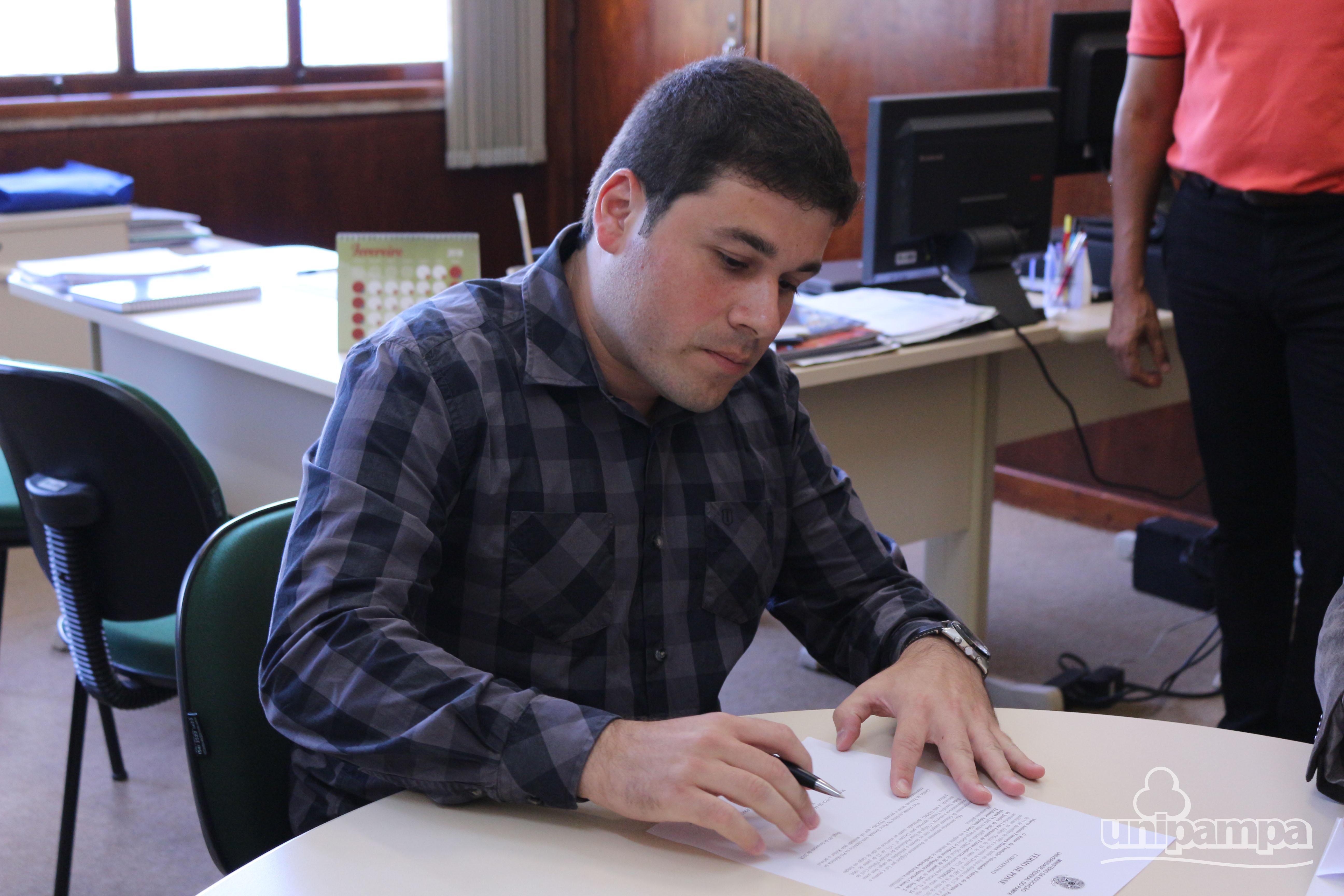 Homem jovem assinando uma folha branca sentada em uma cadeira e apoiada sobre a mesa. Veste camisa xadrez.