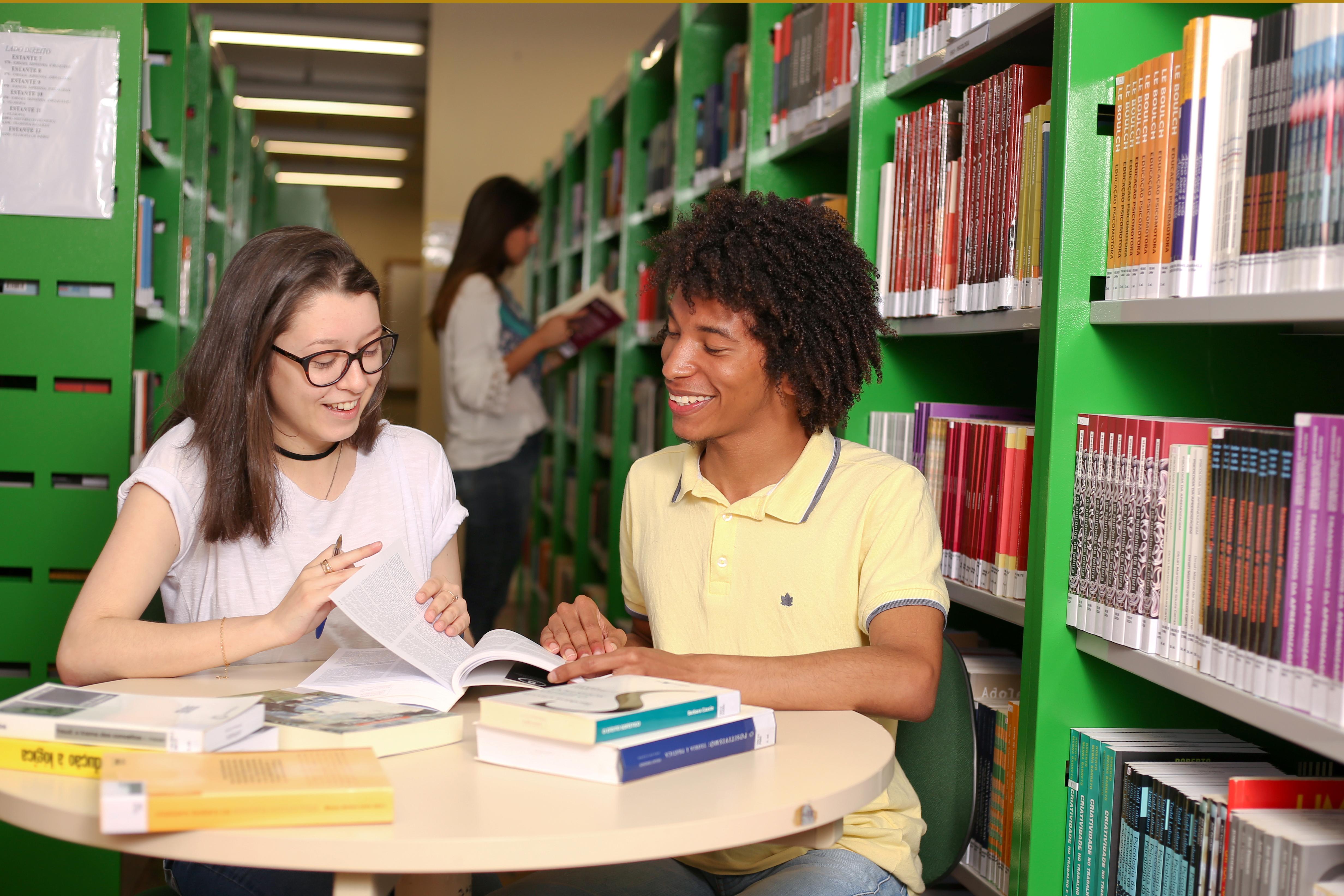 Fundo de estantes de livros. Uma aluna branca e um aluno negro sorrindo e olhando um livro. Ambos sentados.