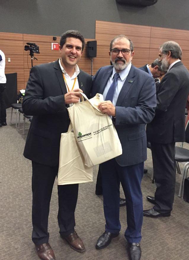 Foto do reitor da Unipampa entregando kit de divulgação da universidade para o reitor da Unila.