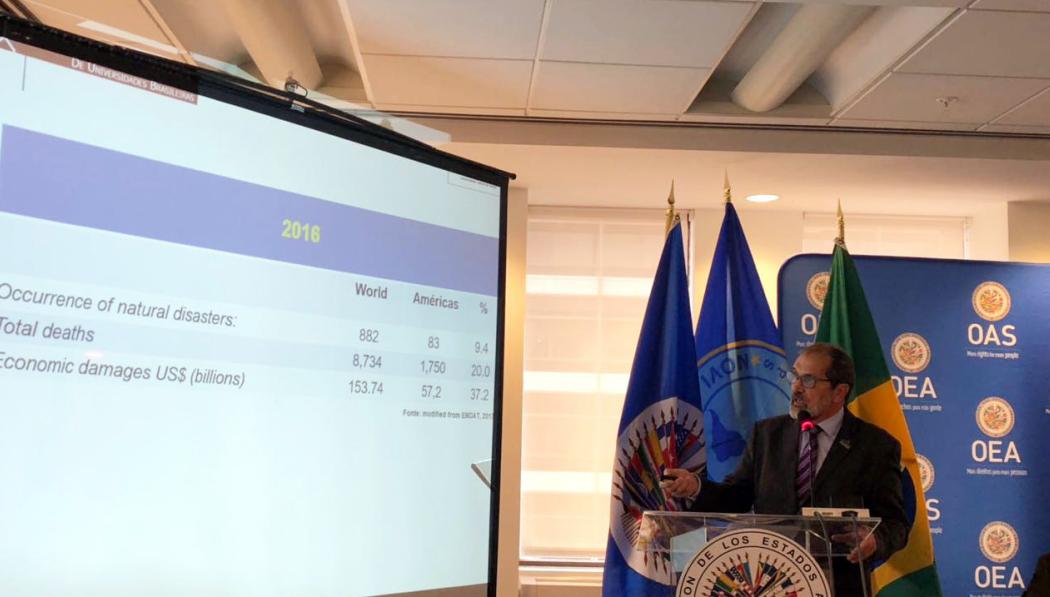 Na foto, o reitor apresenta dados sobre o papel da academia na prevenção e gerenciamento de desastres, apontando para o telão.