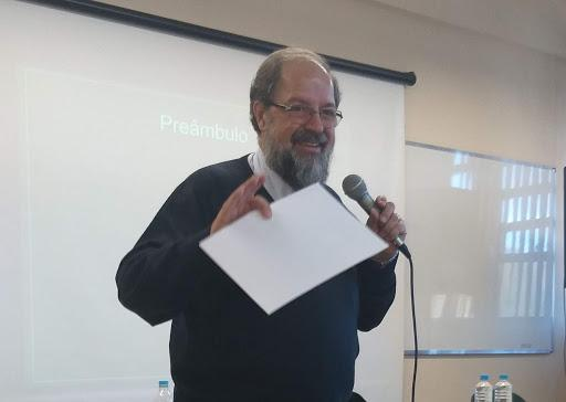 Numa sala de aula, homem grisalho e com barba fala ao microfone