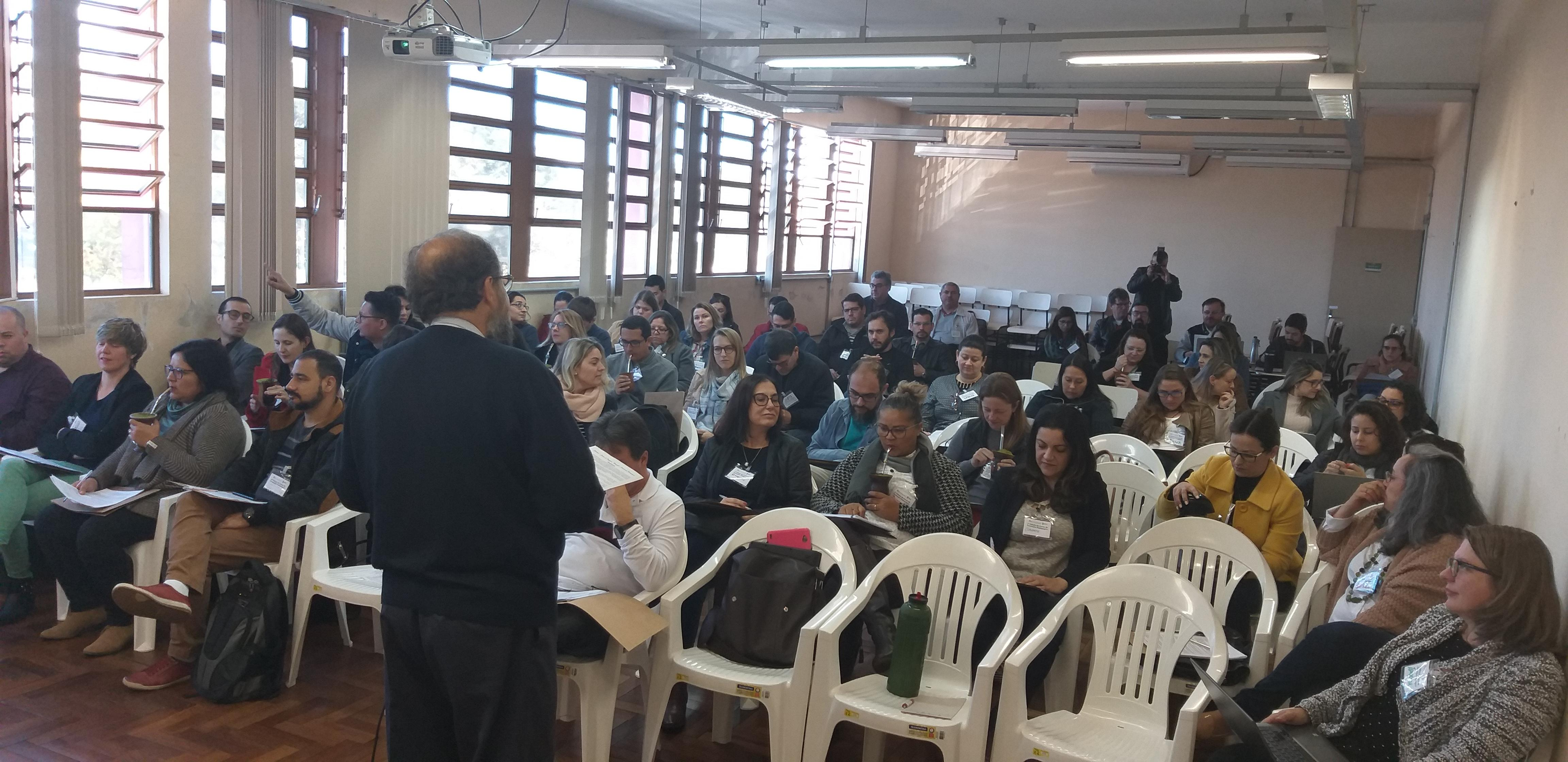 Um professor em pé fala a uma sala cheia durante o curso