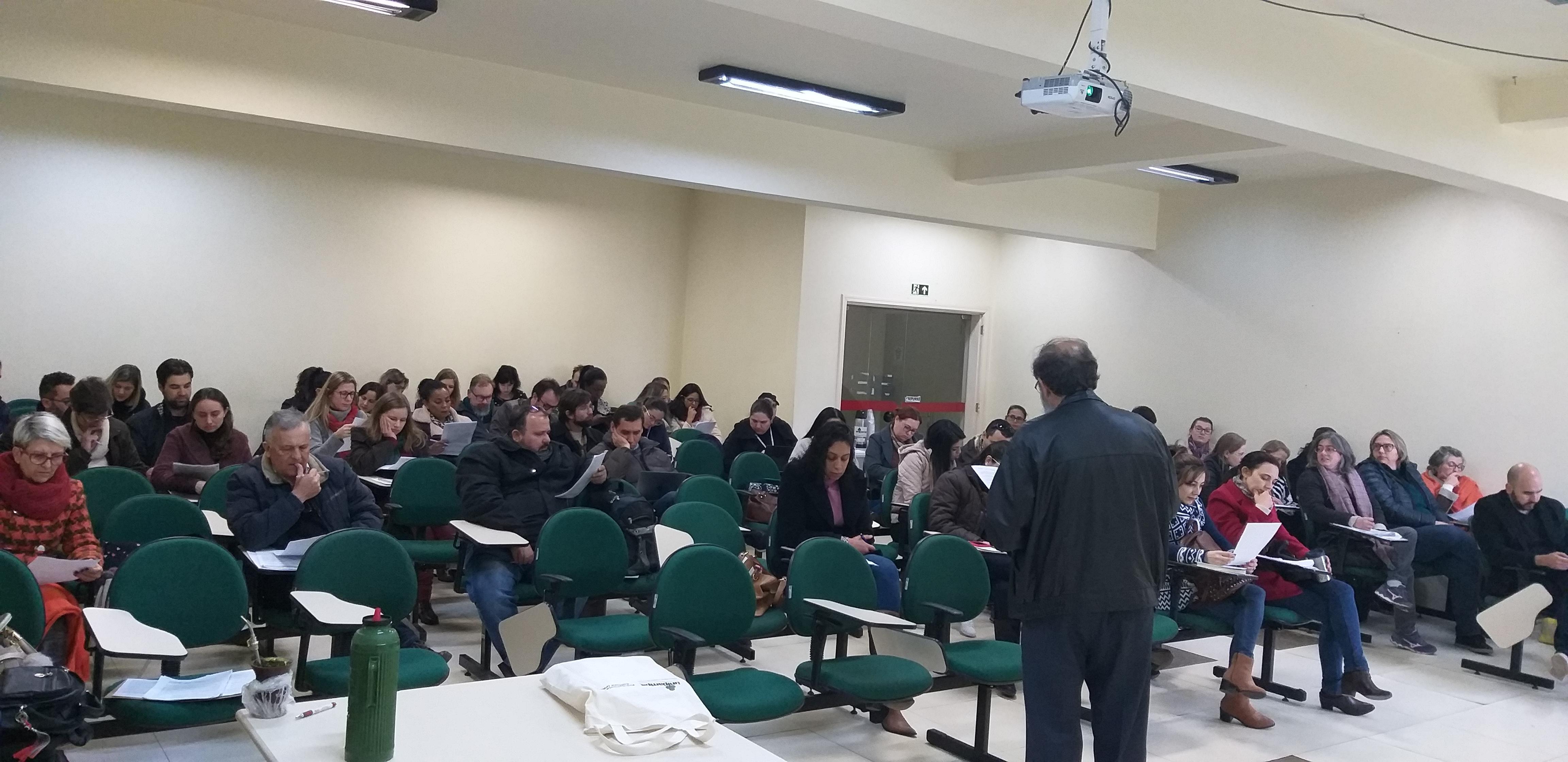 Um professor em pé fala a um auditório durante o curso