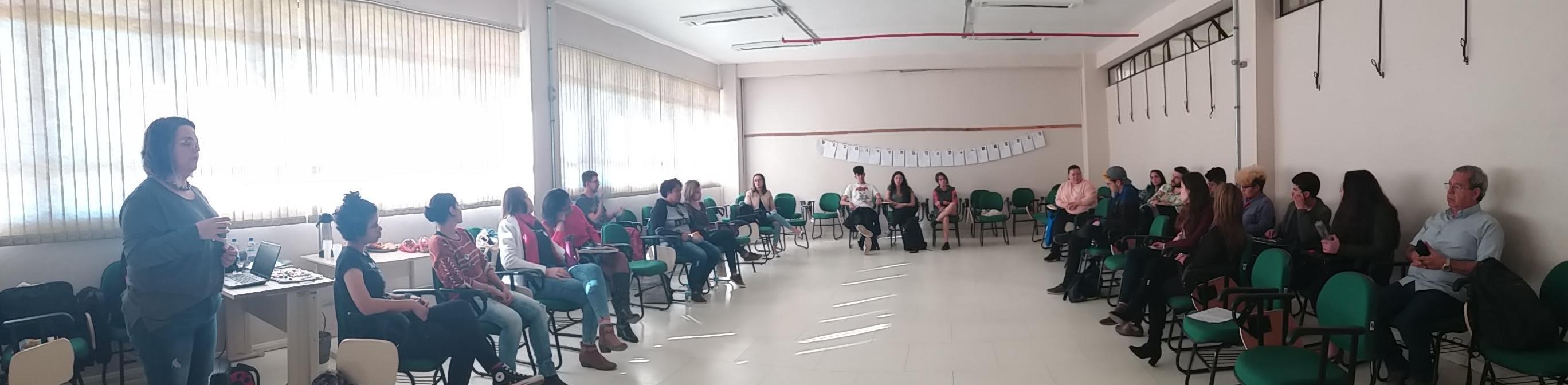 Foto panorâmica de sala com pessoas sentadas organizadas em semicírculo para discussão em grupo