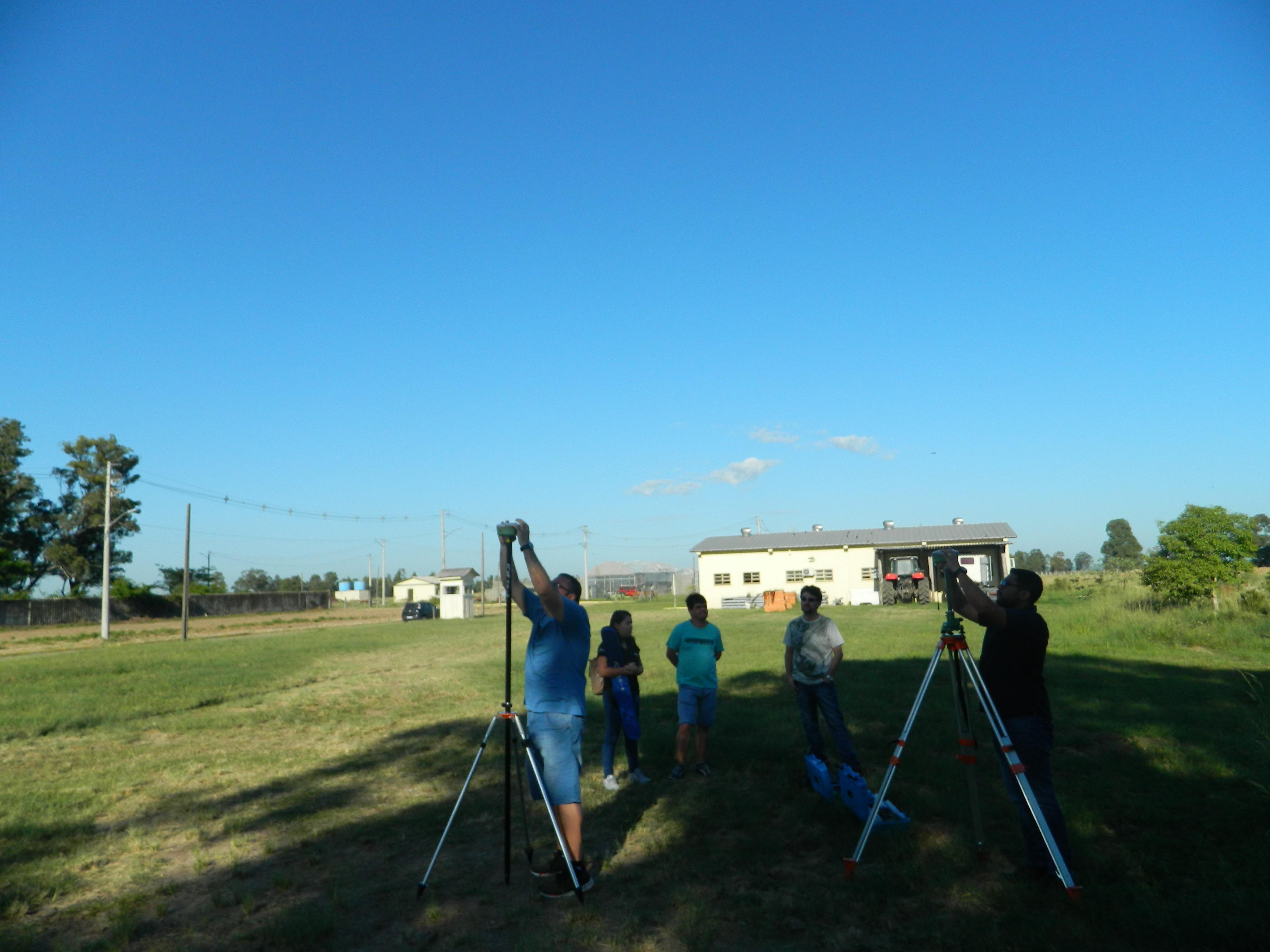 em um campo, dois homens trabalham em equipamentos que parecem tripés. 3 pessoas observam. Ao fundo, ceu azul e garagem e trator