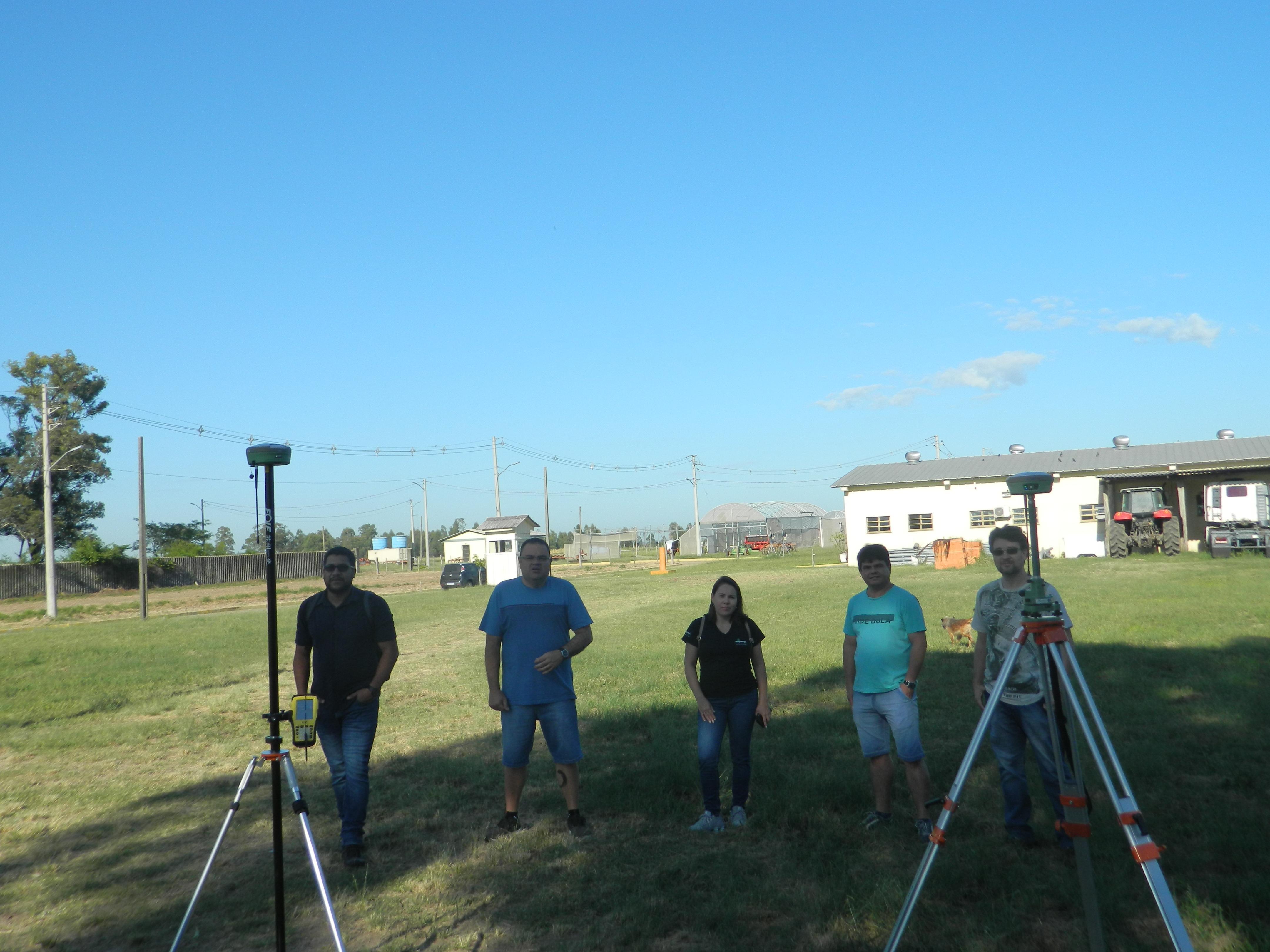 em um campo sob ceu azul, 4 homens e 1 mulher posam entre dois equipamentos que parecem tripés. ao fundo, garagem com trator
