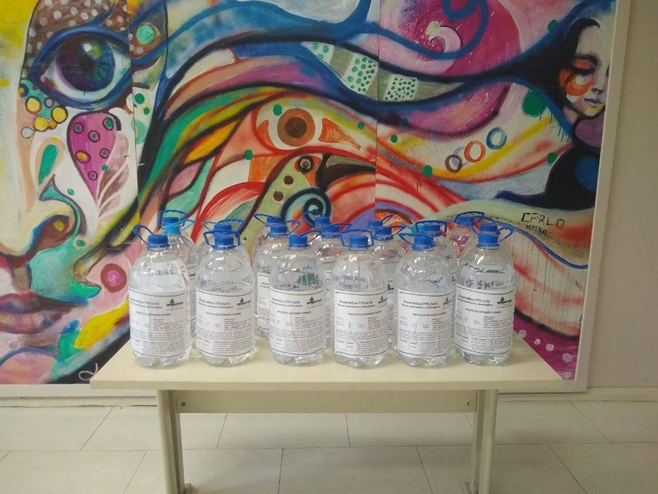 mesa com vários galões de 5l de alcool. ao fundo, obra de arte colorida