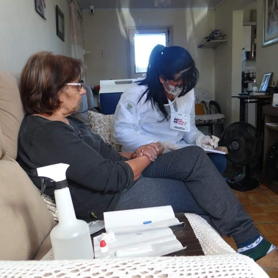 em sala de estar, uma senhora e uma pesquisadora de jaleco sentadas em sofá. Pesquisadora preenche entrevista