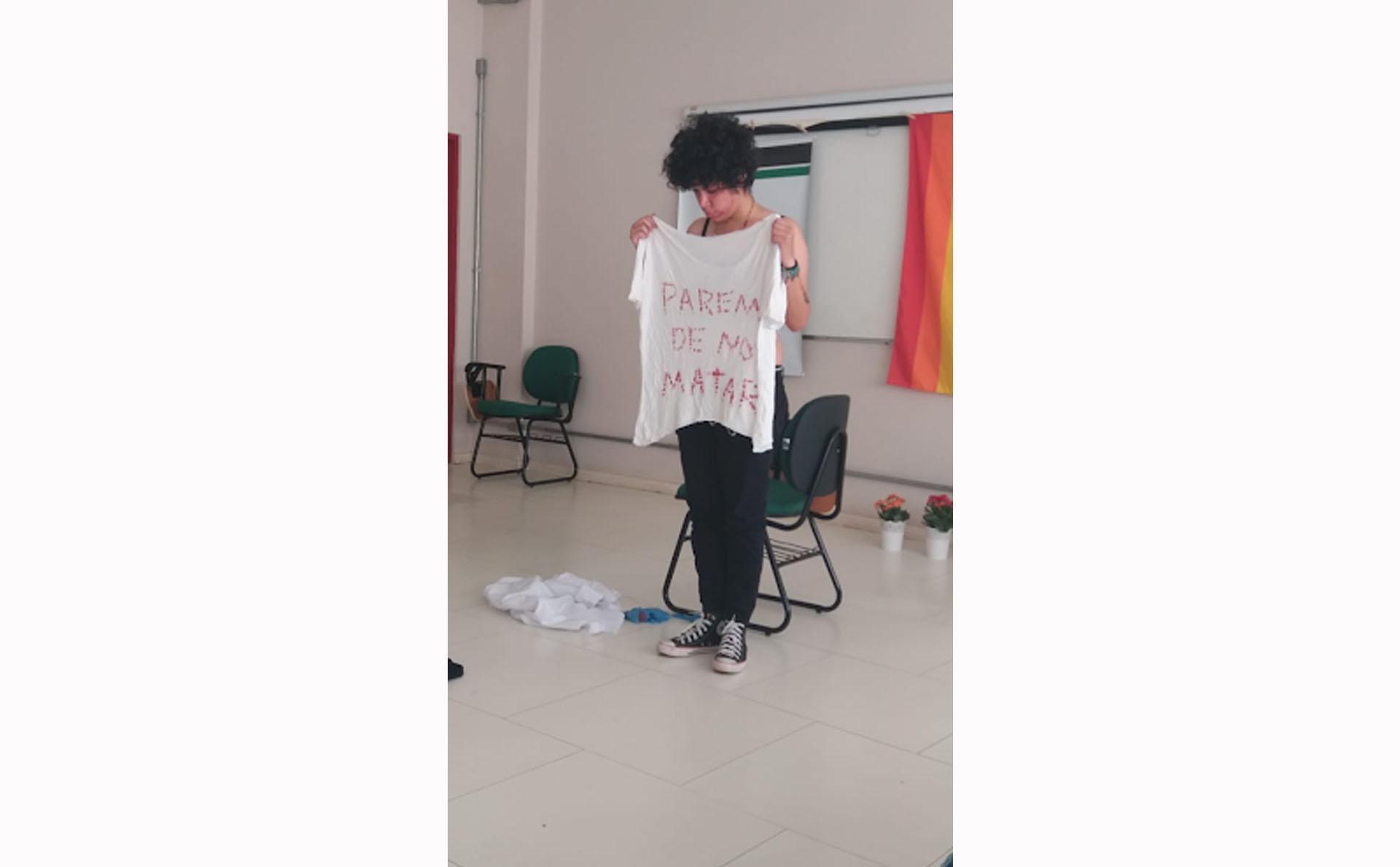 Pessoa segura camiseta branca escrito em vermelho a frase parem de nos matar