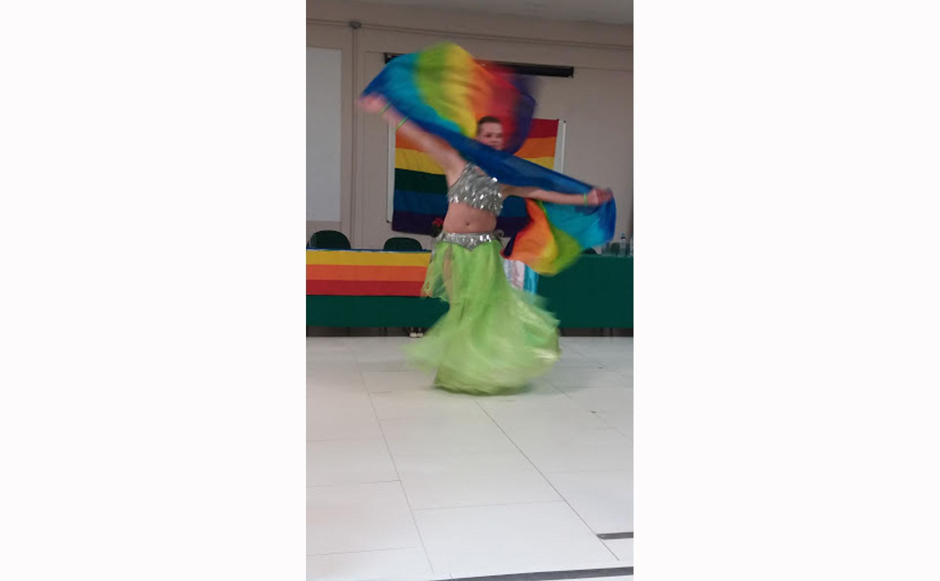 Bailarino apresenta coreografia de dança do ventre em frente à bandeira LGBTQ+