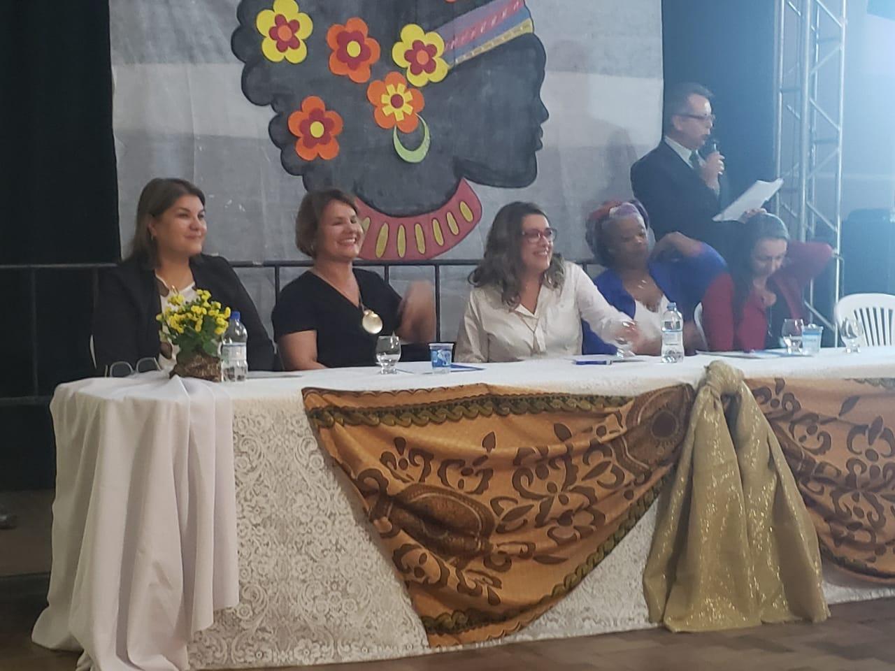 Cinco professoras sentadas enfileiradas na mesa de abertura do evento.