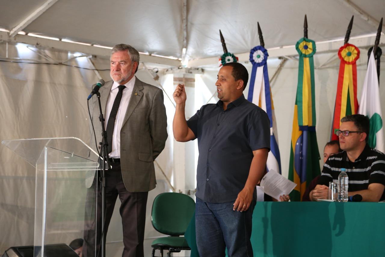 Flávio Alves Monteiro e o intérprete de libras ao lado. Bandeiras do Brasil, Rio grande do Sul, Unipampa e Mercosul ao fundo.