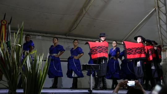 Dez pessoas em pé, dançando. Mulheres com vestidos da cor azul e homens de trajes gaúchos segurando pala vermelho.