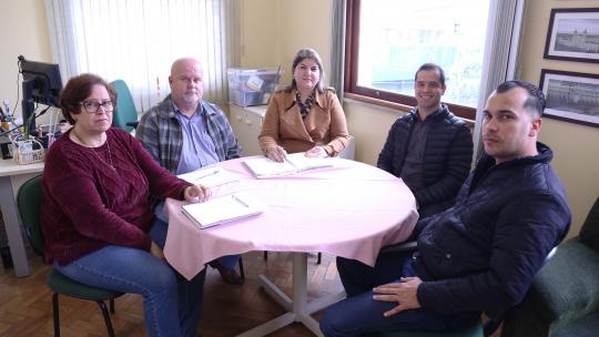 Cincos pessoas sentadas reunidas em torno de uma mesa de reunião redonda.